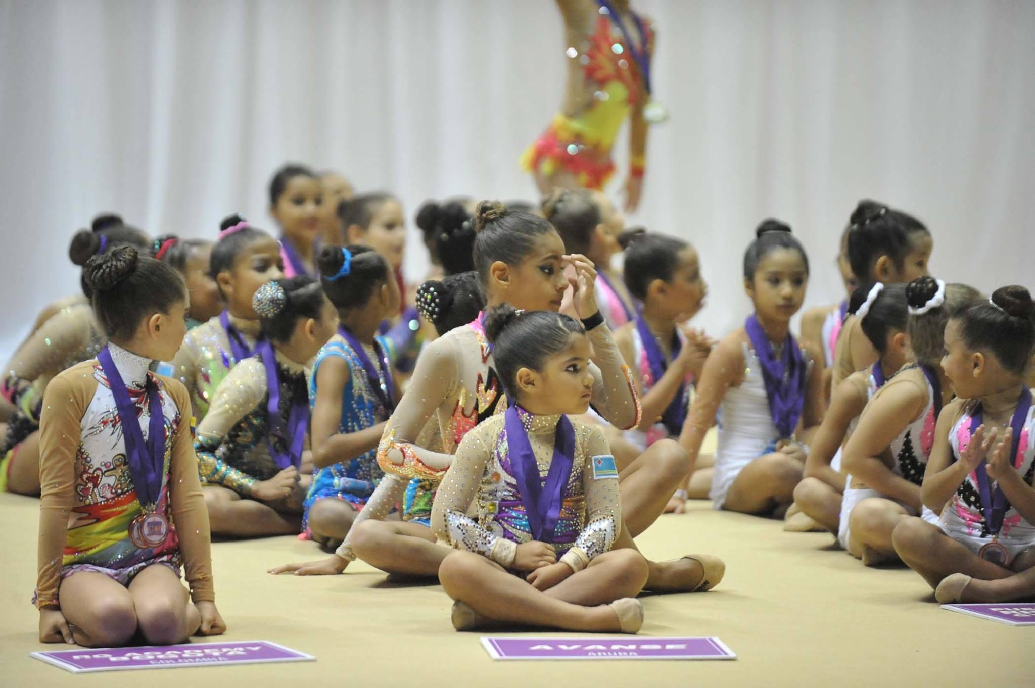 Niñas sentadas en el piso esperando sus premiaciones