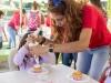 Niñas decorando sus cupcakes con la ayuda del personal a cargo de la actividad
