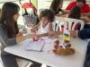 Visitantes creando sus mensajes en corazones de papel