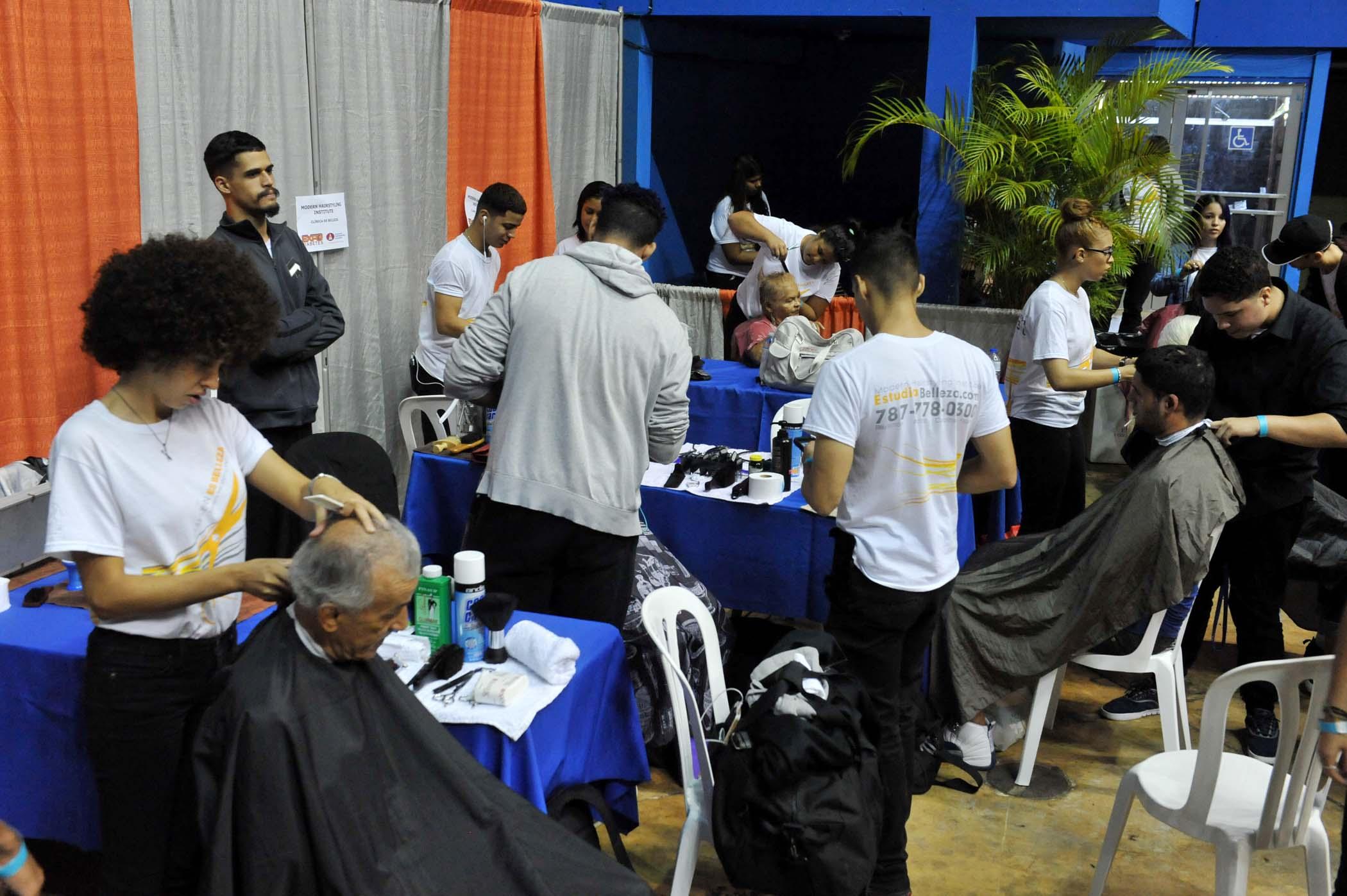 Booth de la Modern Hairstyling Institute ofreciendo recortes y peinados a visitantes de la actividad
