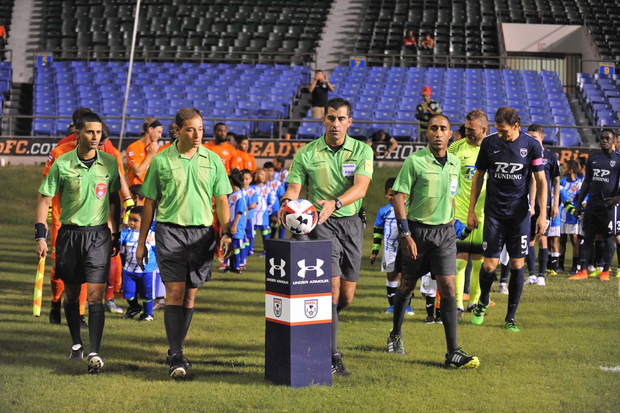 Uno de los referees tomando la pelota para iniciar el juego.