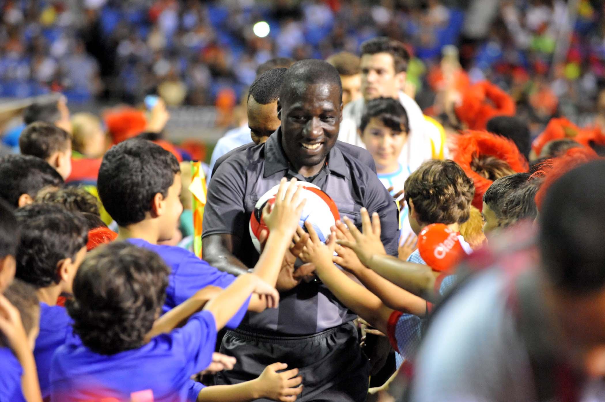 Jugadores  saludando a niños  de pequeñas ligas