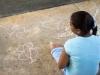 Participante del taller dibujando con tiza en la Plaza de Bayamón