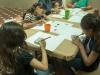 Participantes del taller aprendiendo a hacer obras con gomitas elásticas amarradas a bloques de madera