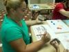 Participante del taller pintando con gomitas elásticas amarradas a bloques de madera