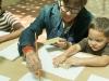 Maestra del taller mostrando a niño como pintar con los bloques de madera