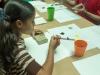 Niña pintando con bloque de madera amarrado con gomitas elásticas