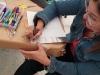 Participante del taller realizando su obra con la técnica de puntillismo