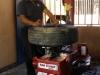 Mecánico haciendo uso de la máquina para montar y desmontar las gomas