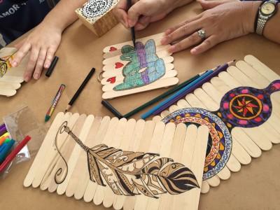Muestra de las obras hechas po los participantes junto a lapices de colores y crayones