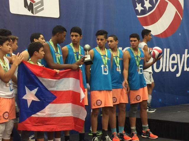 Atletas del Club Voleibol Vaquero mostrando su trofeo y sujetando la bandera de Puerto Rico