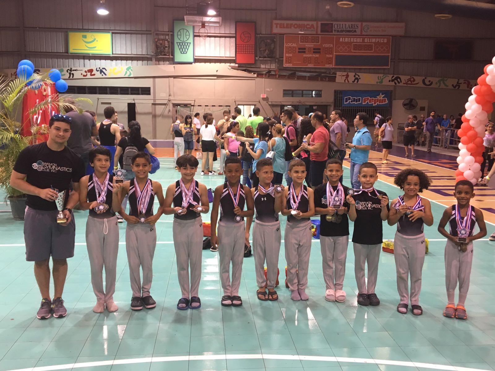 """El pasado 20 y 21 de mayo de 2017 se llevó a cabo la 6ta Copa CGAO (Club Gimnástico Albergue Olímpico), en el Albergue Olímpico de Salinas y el equipo de Bayamon Gymnastic Club logró sobre 76 medallas entre todos los niveles (1 al 5), femenino y masculino. El sábado 20 de mayo, comenzó la competencia con la rama femenina en donde las Vaqueras compitieron en los niveles 1 al 3, logrando sobre 26 medallas para el Club de Bayamón y a su vez el tercer lugar como equipo nivel 3. Lideradas por las entrenadoras Nashua Rivera y Katherine Cintrón, un total de 21 participantes representaron la Ciudad de Bayamón. En las premiaciones de Máximo Acumulador la joven Neymar Maldonado en nivel 3, edad 13up, logró el segundo lugar para su equipo. Akirah Pagán, en el mismo nivel, categoría 12up, se levantó con el tercer lugar de la competencia. En la categoría 10-11, nivel 2, el primer lugar fue para la Vaquera, Sophia Rivera. Kamila Díaz, logró el segundo lugar en la misma rama y categoría y Perla Maldonado el tercer lugar. Los varones entraron a competencia el domingo, 21 de mayo, y su gesta los hizo merecedores del segundo lugar como equipo en la categoría de nivel 4. 11 miembros del equipo de los cuales 10 pertenecen a la Gimnasia Artística Masculina nivel 4 y 1 al nivel 5, demostraron el talento que se cosecha en el Bayamon Gymnastic Club. Los chicos, junto a sus entrenadores Jan Sosa y Luis Natal, lograron un total de 47 medallas para su equipo. 10 de estas fueron primeros lugares, 6 segundos y 9 terceros. El Máximo Acumulador de puntos fue Akim Polanco en la categoría de 5-6 años nivel 4 obteniendo el primer lugar. Yosuet Rivera en la categoría 8-9 años nivel 4 logró el tercer lugar. Zeus Gonzalez en el nivel 4, categoría 10-11, logró el segundo lugar y Luis Berrios en la categoría 12up, nivel 5, se llevó el tercer lugar. """"Se siente bien espectacular, es un orgullo para todos los que formamos parte del Club. Ver como en tan poco tiempo hemos podido levantar tantos jóvenes a tra"""