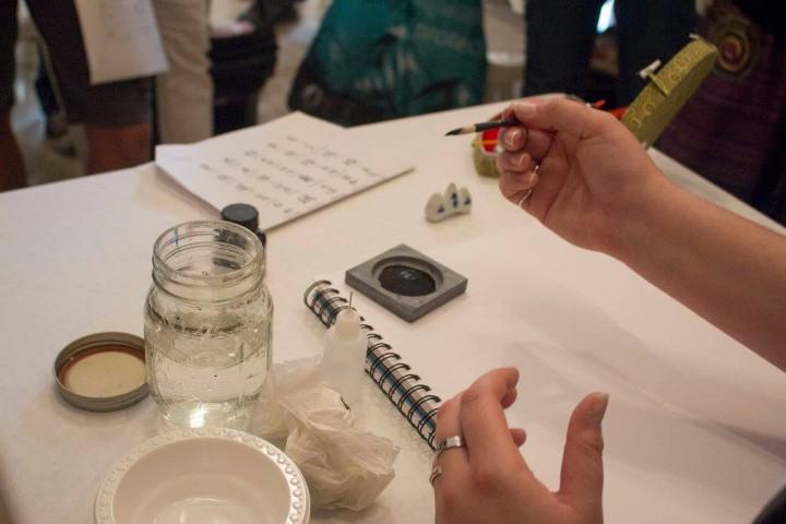 Participantes del taller aprendiendo caligrafía japonesa en el MAB